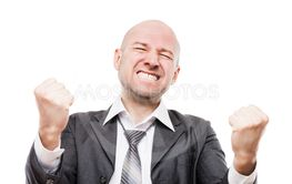 Smiling businessman winner gesturing raised hands fist...
