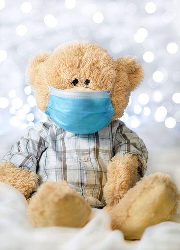 Teddy bear in shirt and blue medical mask