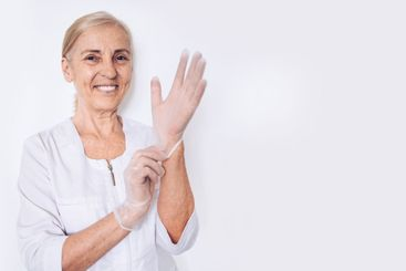 Elderly smiling mature woman doctor or nurse in a white...