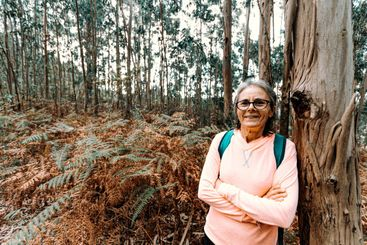 Old woman leaning on a tree while smiling to camera in...
