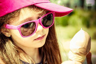 Little girl kid eating ice cream. Summer holidays.