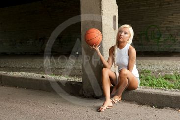 Beautiful blonde girl is sitting with basketball on the...