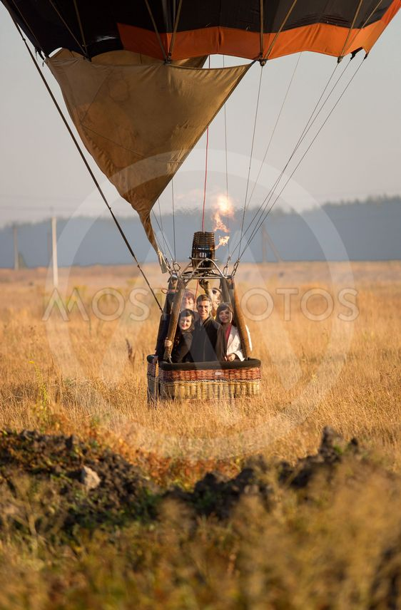 Take off of hot air balloon with crew at field at sunrise
