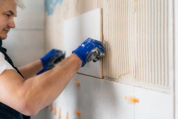 Proffesional tiler installing wall tile at home. Workers...