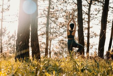Young fit woman doing yoga in the forest during a spring...