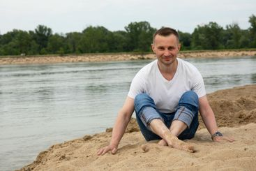 Lonely smile man sitting on the beach river