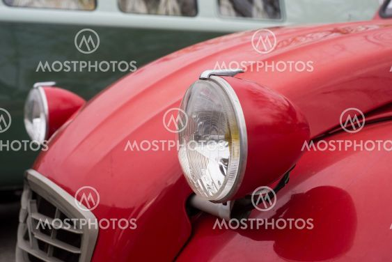 Front light of red Citroen 2CV 6 parked in the street