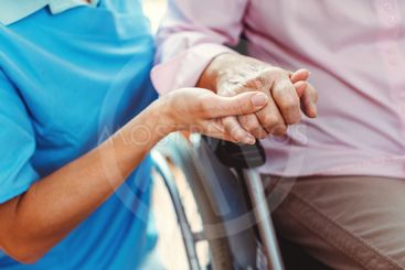 Nurse consoling a senior woman in the nursing home...