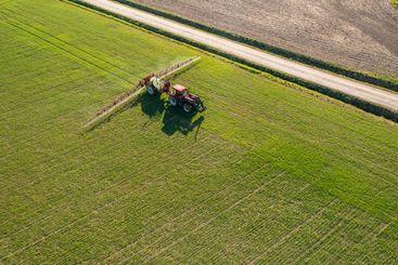 Farmer spraying chemical treatment on field