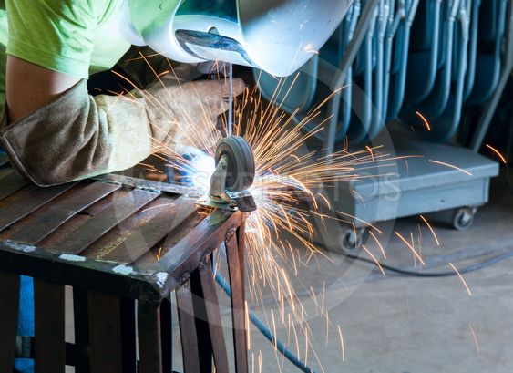 Industrial steel welder in factory working side