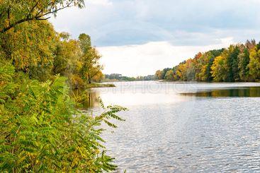 Autumn river landscape against a cloudy sky.