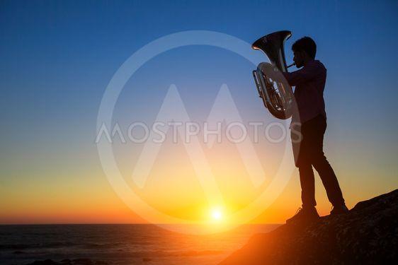 Silhouette of musician play Tuba on sea beach at magical...