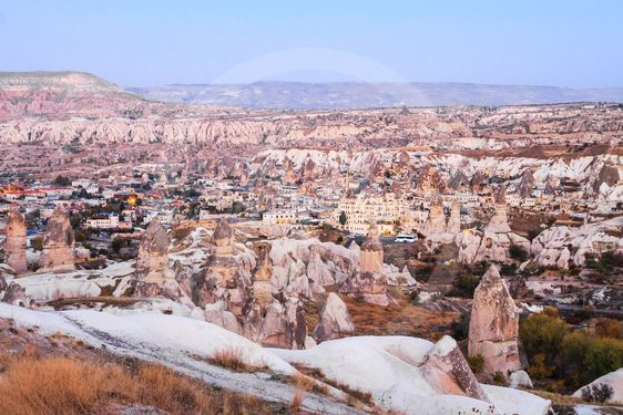 Rock cave and the village in late evening, cappadocia,...