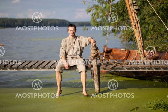Young viking near the drakkar on the lake