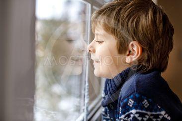 Happy adorable kid boy sitting near window and looking...