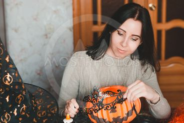Young woman prepares for halloween and keeps masquerade...