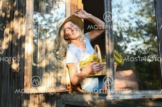 Happy smiling elderly woman having fun posing by open...