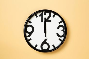 black and white wall clock with large numbers show...