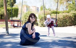 young mother and cute smiling baby girl swinging in park