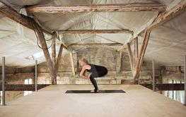 Young woman exercises yoga on an abandoned construction...
