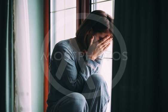 Young sad woman sitting on the window