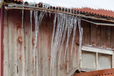 Icicles hanging from a roof on a barn.