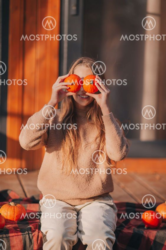 Beautiful girl covered her eyes with pumpkins at autumn...