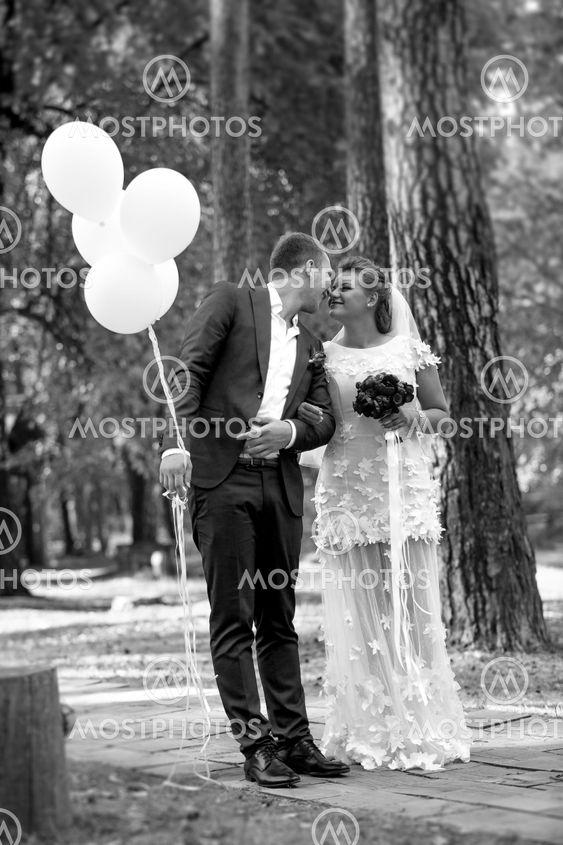 groom holding balloons kissing beautiful bride at park