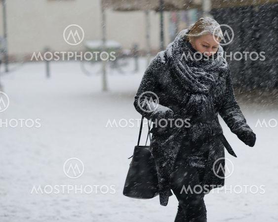 Kvinna vid Slussen, det snöar!