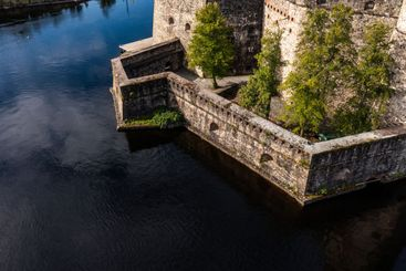 Stone wall of a medieval castle and lake
