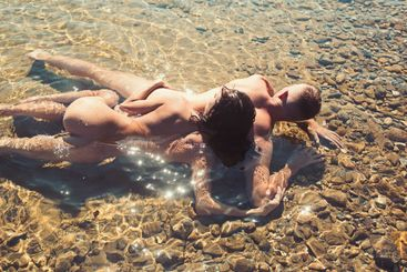 sunset couple sexy kissing love with naked body in water.