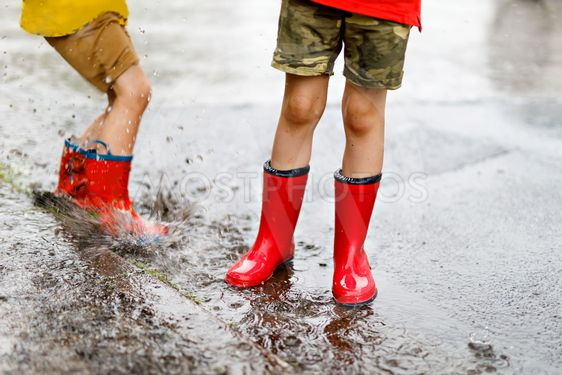 Two children wearing red rain boots jumping into a puddle.