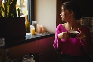 Pretty lady holding red cup and sitting in cafe