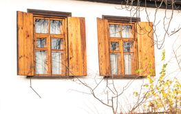 Windows with wooden shutters in a white wall.