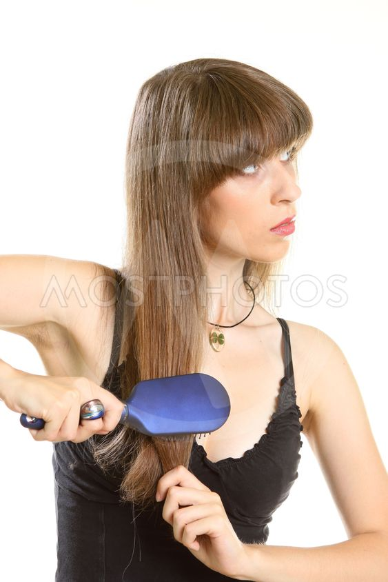 young woman combing her long brown hair with hairbrush