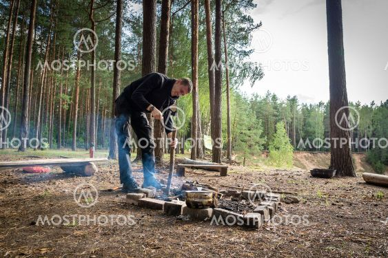 A tourist makes a campfire site in the forest