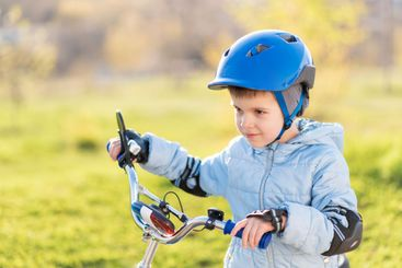 A child in a helmet learns to ride a bike on a sunny day...