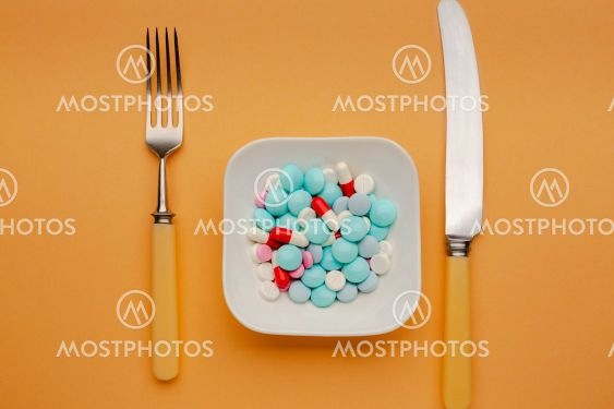 White plate with different pills on it with knife and fork