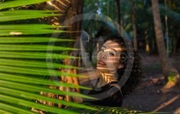 Young woman of mixed race among the leaves of palm trees.