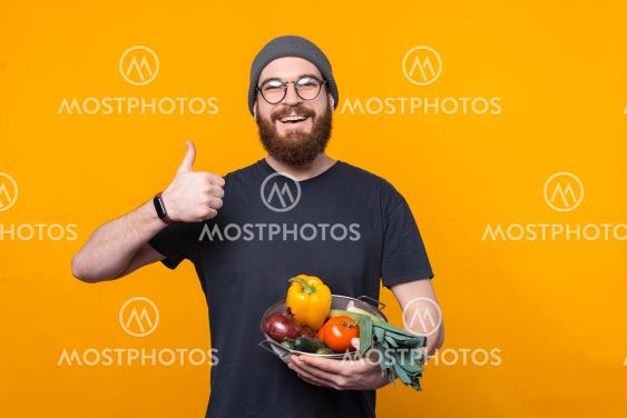 Photo of young farmer showing thumb up and holding fresh...
