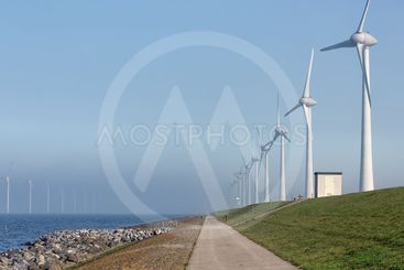 Wind turbines along Dutch dike in Flevoland near Urk