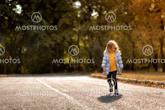 little girl in coat in autumn plays with toy car on...