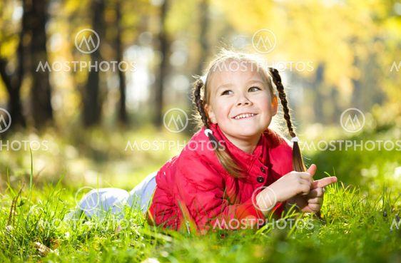 Portræt af en lille pige i efteråret park