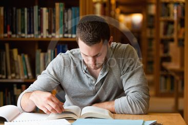 Male student researching with a book