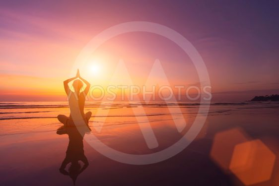 Silhouette of a girl in a pose of yoga on a beautiful...