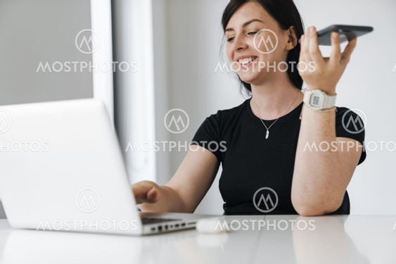 Confident young business woman working on laptop