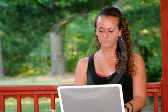 Teen Girl Behind Laptop Outdoors (Horizontal)
