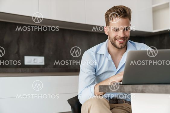 Handsome cheerful guy working with laptop while sitting