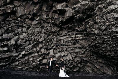 Destination Iceland wedding. Wedding couple under a rock...