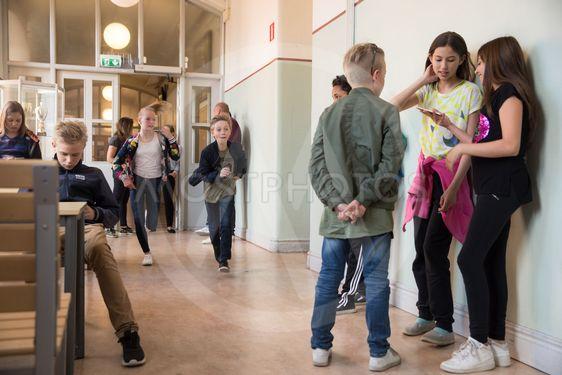 barn springer genom skolkorridor